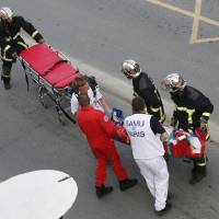 Photo - Rescue workers transport a victim from a train that derailed in Bretigny sur Orge, south of Paris, Friday July, 12, 2013. A packed passenger train skidded off its rails after leaving Paris on Friday, leaving seven people believed dead and dozens injured as train cars slammed into each other and overturned, authorities said. (AP Photo/Jacques Brinon)