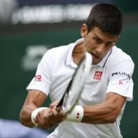 Photo - Novak Djokovic of Serbia plays a return to Andrey Golubev of Kazakhstan during their first round match at the All England Lawn Tennis Championships in Wimbledon, London,  Monday, June  23, 2014. (AP Photo/Pavel Golovkin)