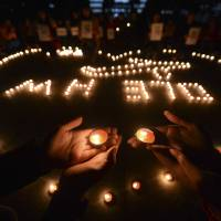 Photo - In this March 13, 2014 file photo, university students hold a candlelight vigil for passengers on the missing Malaysia Airlines Flight MH370 in Yangzhou, in eastern China's Jiangsu province. The disappearance of Malaysia Airlines Flight 370 has exposed wide gaps in how the world's airlines, and their regulators, operate. But experts warn this isn't likely to be one of those defining moments that lead to fundamental changes. (AP Photo/File)  CHINA OUT