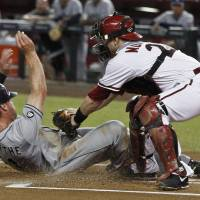Photo -   San Diego Padres' Logan Forsythe, left, scores a run as he slides under the tag of Arizona Diamondbacks' Miguel Montero during the first inning during a baseball game Tuesday, Sept. 18, 2012, in Phoenix. (AP Photo/Ross D. Franklin)