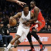 Photo - Brooklyn Nets guard Joe Johnson, left, tries to drive past Chicago Bulls forward Luol Deng in the first half of Game 2 of their first-round NBA basketball playoff series, Monday, April 22, 2013, in New York. (AP Photo/Kathy Willens)