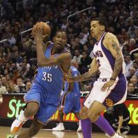 Photo - Oklahoma City Thunder forward Kevin Durant, left, drives to the basket against Phoenix Suns forward Matt Barnes in the first quarter of an NBA basketball game Friday, Feb 20, 2009, in Phoenix. (AP Photo/Paul Connors) ORG XMIT: PNU102