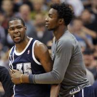 Photo - Oklahoma City Thunder's Hasheem Thabeet, right, of Tanzania, holds back small forward Kevin Durant (35) after Durant was called for a technical foul during the fourth quarter of an NBA basketball game against the Minnesota Timberwolves at the Target Center on Thursday, Dec. 20, 2012, in Minneapolis. The Timberwolves won 99-93. (AP Photo/Hannah Foslien) ORG XMIT: MNHF110