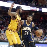 Photo - Indiana Pacers' Paul George (24) drives past Cleveland Cavaliers' Earl Clark during the first quarter of an NBA basketball game Sunday, Jan. 5, 2014, in Cleveland. (AP Photo/Tony Dejak)