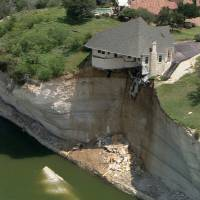Photo - In this image taken from video provided June 12, 2014, by WFAA.Com, a luxury house teeters on a cliff about 75 feet above Lake Whitney in Whitney, Texas. The owner of a vacant luxury house teetering on a crumbling 75-foot cliff over a Central Texas lake has decided to burn the house and clear the lot of the debris. (AP Photo/WFAA.Com)
