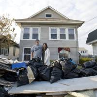 Photo -   Jared and Sarah Lenko stand in front of their Ocean City, N.J. house on Saturday, Nov. 10 2012 that was under two feet of water during Superstorm Sandy. (AP Photo/The Press of Atlantic City, Matthew Strabuk)