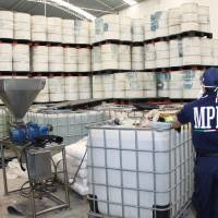 Photo -   FILE - In this June 20, 2011, photo released by Mexico's Attorney General's office, police from the Federal Public Ministry looks at drums of precursor chemicals for methamphetamine that were seized in Queretaro, Mexico. Mexican drug cartels are flooding U.S. cities with cheap, extraordinarily pure methamphetamine made in factory-like