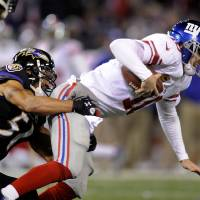 Photo - New York Giants quarterback Eli Manning, right, is sacked by Baltimore Ravens inside linebacker Brendon Ayanbadejo in the first half of an NFL football game in Baltimore, Sunday, Dec. 23, 2012. (AP Photo/Nick Wass)