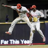 Photo - Philadelphia Phillies' Tony Gwynn and Domonic Brown (9) celebrate after a baseball game against the Milwaukee Brewers Monday, July 7, 2014, in Milwaukee. The Phillies won 3-2. (AP Photo/Morry Gash)