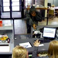 Photo - A robber points a weapon at tellers at a Bank of  Oklahoma branch, 4324 SE 44, in Oklahoma City.  PHOTOS PROVIDED