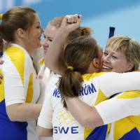 Photo - Sweden's Maria Prytz, far right, gets a hug from Maria Wennerstroem after her final throw during women's curling competition against the United States at the 2014 Winter Olympics, Saturday, Feb. 15, 2014, in Sochi, Russia. Christina Bertrup, far left, hugs Margaretha Sigfridsson. (AP Photo/Robert F. Bukaty)
