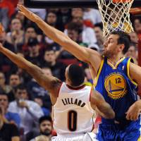 Photo - Portland Trail Blazers guard Damian Lillard (0) drives to the basket on Golden State Warriors center Andrew Bogut (12) during the first half of an NBA basketball game in Portland, Ore., Sunday, April 13, 2014. (AP Photo/Steve Dykes)