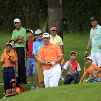 Photo - Lee Westwood, center, of England watches his shot on the fifth hole during the third round of the Malaysian Open golf tournament at Kuala Lumpur Golf and Country Club in Kuala Lumpur, Malaysia, Saturday, April 19, 2014. (AP Photo/Lai Seng Sin)