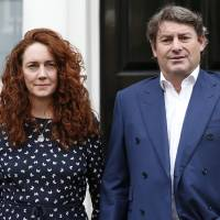 Photo - Rebekah Brooks, left, former News International chief executive, accompanied by her husband Charlie, right, pose for the photographers as she arrives to talk to members of the media, in central London, Thursday, June 26, 2014. Brooks was acquitted after a near 8 month long trial centering on illegal activity at the heart of Rupert Murdoch's newspaper empire but Former News of the World editor Andy Coulson was convicted of phone hacking. The nearly eight-month trial was triggered by revelations that for years the News of the World used illegal eavesdropping to get stories, listening in on the voicemails of celebrities, politicians and even crime victims. (AP Photo/Lefteris Pitarakis)