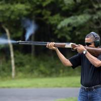 Photo - In this photo released by the White House, President Barack Obama shoots clay targets on the range at Camp David, Md., Saturday, Aug. 4, 2012. The White House released a photo of Obama firing a gun, two days before he heads to Minnesota to discuss gun control. In a recent interview with The New Republic magazine, Obama said yes when asked if he has ever fired a gun. He said