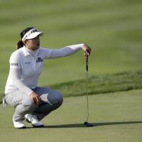 Photo - Amy Yang of South Korea lines up a putt on the ninth hole during the first round of the LPGA KEB Hana Bank Championship golf tournament at Sky72 Golf Club in Incheon, west of Seoul, South Korea, Friday, Oct. 18, 2013. Yang finished her first round in the lead with Katherine Hull-Kirk of Australia, Park Ju-young of South Korea and Anna Nordqvist of Sweden, with a five-under par 67. (AP Photo/Lee Jin-man)