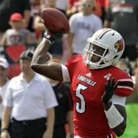 Photo - Louisville quarterback Teddy Bridgewater (5) launches a pass during the first quarter of an NCAA college football game against Ohio University in Louisville, Ky., Sunday, Sept. 1, 2013. (AP Photo/Garry Jones)