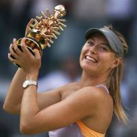 Photo - Maria Sharapova from Russia celebrates her victory holding her trophy after a Madrid Open tennis tournament final match against  Simona Halep from Romania in Madrid, Spain, Sunday, May 11, 2014. (AP Photo/Andres Kudacki)