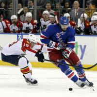 Photo - Florida Panthers' Scottie Upshall (19) battles for the puck against New York Rangers' Nick Rash during the second period of an NHL hockey game Thursday, April 18, 2013 at Madison Square Garden in New York. (AP Photo/Mary Altaffer)