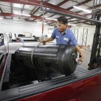 Photo -  Technician John Kline positions a new CNG tank Thursday during installation in a vehicle at Heartland Energy Options in Oklahoma City.  Photos by Paul B. Southerland, The Oklahoman   PAUL B. SOUTHERLAND -