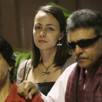 Photo - Dutch rebel Tanja Nijmeijer, from the Revolutionary Armed Forces of Colombia, or FARC, center, arrives with Jesus Santrich, right, for peace talks with negotiators from Colombia's government in Havana, Cuba, Saturday, Jan. 19, 2013.  Nijmeijer, 34, is a middle-class child of the Netherlands who for the past decade has been mixed up in a Latin American revolution as a jungle fighter, at least once narrowly escaping death in a military bombardment.  (AP Photo/Ismael Francisco, Cubadebate)