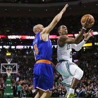Photo - Boston Celtics guard Rajon Rondo, right, drives to the basket against New York Knicks guard Jason Kidd during the second quarter of an NBA basketball game in Boston, Thursday, Jan. 24, 2013. (AP Photo/Charles Krupa)