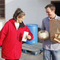 Photo - Volunteer Daniel Holdge helps Deborah Wood during the annual Easter food basket distribution at the Jesus House. Photos By Paul Hellstern, The Oklahoman