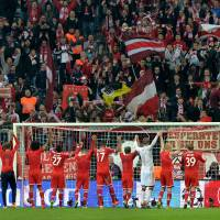 Photo - Bayern's players celebrate with supporters after the Champions League quarterfinal second leg soccer match between Bayern Munich and Manchester United in the Allianz Arena in Munich, Germany, Wednesday, April 9, 2014. Munich defeated Manchester by 3-1. (AP Photo/Kerstin Joensson)