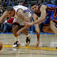 Photo - Oklahoma City's Thabo Sefolosha chases down the ball in front of New Yorki's Landry Fields during the NBA game between the the Oklahoma City Thunder and the New York Knicks at the Oklahoma City Arena in Oklahoma City on Saturday. (Photo by Bryan Terry, The Oklahoman)
