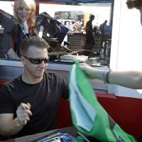 Photo - AJ Allmendinger signs autographs for fans before the Grand-Am Series Rolex 24 hour auto race at Daytona International Speedway, Saturday, Jan. 26, 2013, in Daytona Beach, Fla. (AP Photo/John Raoux)