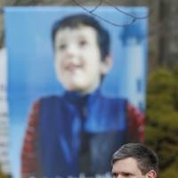 Photo - A mourner wears a photograph of Benjamin Andrew Wheeler, one of the students killed in the Sandy Hook Elementary School shooting last week, as a large portrait of Wheeler stands outside of Trinity Episcopal Church after funeral services, Thursday, Dec. 20, 2012, in Newtown, Conn. Wheeler, 6, died when the gunman, Adam Lanza, walked into Sandy Hook Elementary School in Newtown, Dec. 14, and opened fire, killing 26 people, including 20 children, before killing himself. (AP Photo/Julio Cortez)