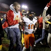 Photo - Iowa State fans rush the field past Oklahoma State's' Brodrick Brown (19) after OSU's 37-31 double-overtime loss in a college football game between the Oklahoma State University Cowboys (OSU) and the Iowa State University Cyclones (ISU) at Jack Trice Stadium in Ames, Iowa, Friday, Nov. 18, 2011. Photo by Bryan Terry, The Oklahoman