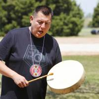 Photo - Everett Moore, of Jones, sings and beats a drum to accompany American Indian dancers during a Red Earth Day event at King's Gate Christian School.