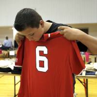 Photo - Nathan Davis, 13, checks the six of shirt as he finds clothes at Southern Hills Baptist Church, Friday, June 21, 2013, in Oklahoma City. Davis' home has damaged in the May 20 tornado. Photo by Sarah Phipps, The Oklahoman