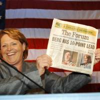 Photo - FILE - In this Nov. 7, 2012, file photo, Democratic candidate for North Dakota's U.S. Senate seat, Heidi Heitkamp, holds up the Oct. 20, 2012, Fargo Forum  in Bismarck, N.D., showing the newspaper had Heitkamp's challenger Republican Rick Berg leading Heitkamp in the state by ten points. The grueling political showdown between Heitkamp and Berg in the hotly contested race for U.S. Senate ranked as North Dakota's top news story of 2012, according to a vote by Associated Press newspaper and broadcast members. (AP Photo/Will Kincaid, File)