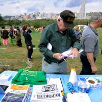 Photo -   A man signs a petition during a global Frackdown Day calling for a moratorium on Shale Gas Drilling at Schenley Park in Pittsburgh, Saturday, Sept. 22, 2012. (AP Photo/John Heller)