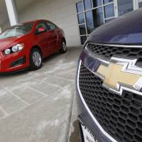 Photo -   FILE - This Feb. 19, 2012 file photo shows the familiar Chevrolet bowtie logo displayed on the grille of a 2012 Cruze sedan, foreground, with a 2012 Sonic sedan in the background at a Chevrolet dealership in the south Denver suburb of Englewood, Colo. Sunday, Nov. 18, 2012, marks the anniversary of GM's initial public stock offering in November 2010. The company has made money for 11 straight quarters, piling up more than $16 billion in profits. Its cars and trucks are selling for good prices. And sales are strong in China. (AP Photo/David Zalubowski, File)