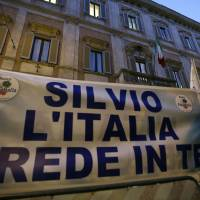 Photo - Supporters of former Italian premier Silvio Berlusconi expose a banner reading