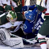 Photo - Vancouver Canucks left wing Mason Raymond (21) crashes into Minnesota Wild goalie Darcy Kuemper (35) during the second period of an NHL hockey game, Tuesday, Feb. 12, 2013, in Vancouver, British Columbia. (AP Photo/The Canadian Press, Jonathan Hayward)