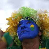 Photo - A fan of the Brazil national soccer team watches a live broadcast of the World Cup third-place soccer match between Brazil and Netherlands, inside the FIFA Fan Fest area on Copacabana beach, in Rio de Janeiro, Brazil, Saturday, July 12, 2014. (AP Photo/Silvia Izquierdo)