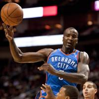 Photo - Oklahoma City Thunder's Kendrick Perkins drives between Houston Rockets' Kyle Lowry (7) and Kevin Martin, right, during the first quarter of an NBA basketball game, Wednesday, Feb. 15, 2012, in Houston. (AP Photo/Dave Einsel)