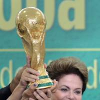 Photo - FILE - In this June 2, 2014 file photo, Brazil's President Dilma Rousseff holds up the 2014 World Cup trophy after it was officially presented to Rousseff by FIFA President Sepp Blatter, during a ceremony at the Planalto presidential palace, in Brasilia, Brazil. Rousseff met Friday, July 11, 2014 with a group of foreign journalists in Brasilia, where she hailed Brazil proved skeptics wrong who said the nation couldn't organize a successful World Cup, and said it boded well for its hosting of the 2016 Summer Olympics in Rio de Janeiro. (AP Photo/Eraldo Peres, File)