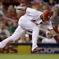 Photo - St. Louis Cardinals third baseman Matt Carpenter cannot reach a ball hit for a single by Milwaukee Brewers' Carlos Gomez during the fifth inning of a baseball game Friday, Aug. 1, 2014, in St. Louis. (AP Photo/Jeff Roberson)