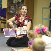 Photo - Children's assistant librarian Beverly Theige reads a story to children at a Music Connection program at the Norman Public Library. PHOTO PROVIDED BY NORMAN PUBLIC LIBRARY