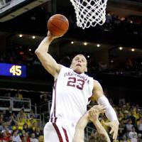 Photo - OU / UNIVERSITY OF OKLAHOMA / NCAA TOURNAMENT / DUNK: OU's Blake Griffin dunks the ball over Michigan's Zack Novak during a second-round men's NCAA college basketball tournament game between Oklahoma and Michigan in Kansas City, Mo., Saturday, March 21, 2009. PHOTO BY BRYAN TERRY, THE OKLAHOMAN ORG XMIT: KOD