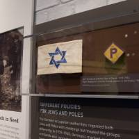Photo - This Thursday, April 25, 2013 photo shows an armband with the Star of David and a badge for a forced laborer in Germany at the United States Holocaust Memorial Museum during a preview of the new exhibit