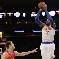 Photo - New York Knicks' Carmelo Anthony (7) shoots over Los Angeles Clippers' Blake Griffin (32) during the first half of an NBA basketball game on Sunday, Feb. 10, 2013, in New York. (AP Photo/Frank Franklin II)