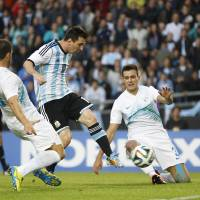 Photo - Argentina's Lionel Messi, center, scores past Slovenia's Miral Samardzic, right, and Bojan Jokic during their international friendly soccer match in La Plata, Argentina, Saturday, June 7, 2014. Argentina's team is leaving June 9 for Brazil to compete in the World Cup. (AP Photo/Natacha Pisarenko)