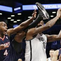 Photo - Atlanta Hawks forward Anthony Tolliver (4) tries to get the referee's attention as he becomes entangled with Brooklyn Nets forward Andray Blatche (0) in the first half of their NBA basketball game at the Barclays Center, Friday, Jan. 18, 2013, in New York. (AP Photo/Kathy Willens)