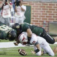 Photo - SMU quarterback Neal Burcham (12) fumbles the ball as he is hit by Baylor defensive lineman Beau Blackshear (95) and linebacker Aiavion Edwards (20) during the first half of an NCAA college football game Sunday, Aug. 31, 2014, in Waco, Texas.  The ball went out of bounds so SMU retained possession. (AP Photo/LM Otero)